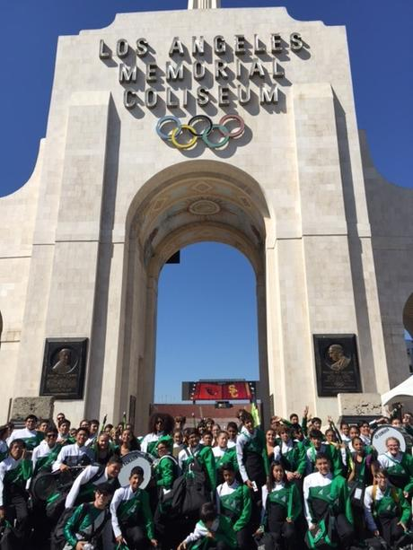 Marching band poses at LA Coliseum arc at USC band day football game